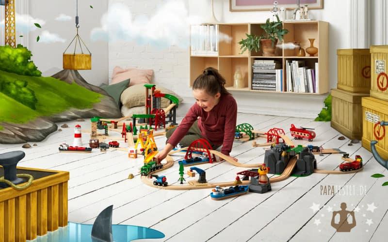 Ein Kind spielend auf dem Boden mit der BRIO Holzeisenbahn