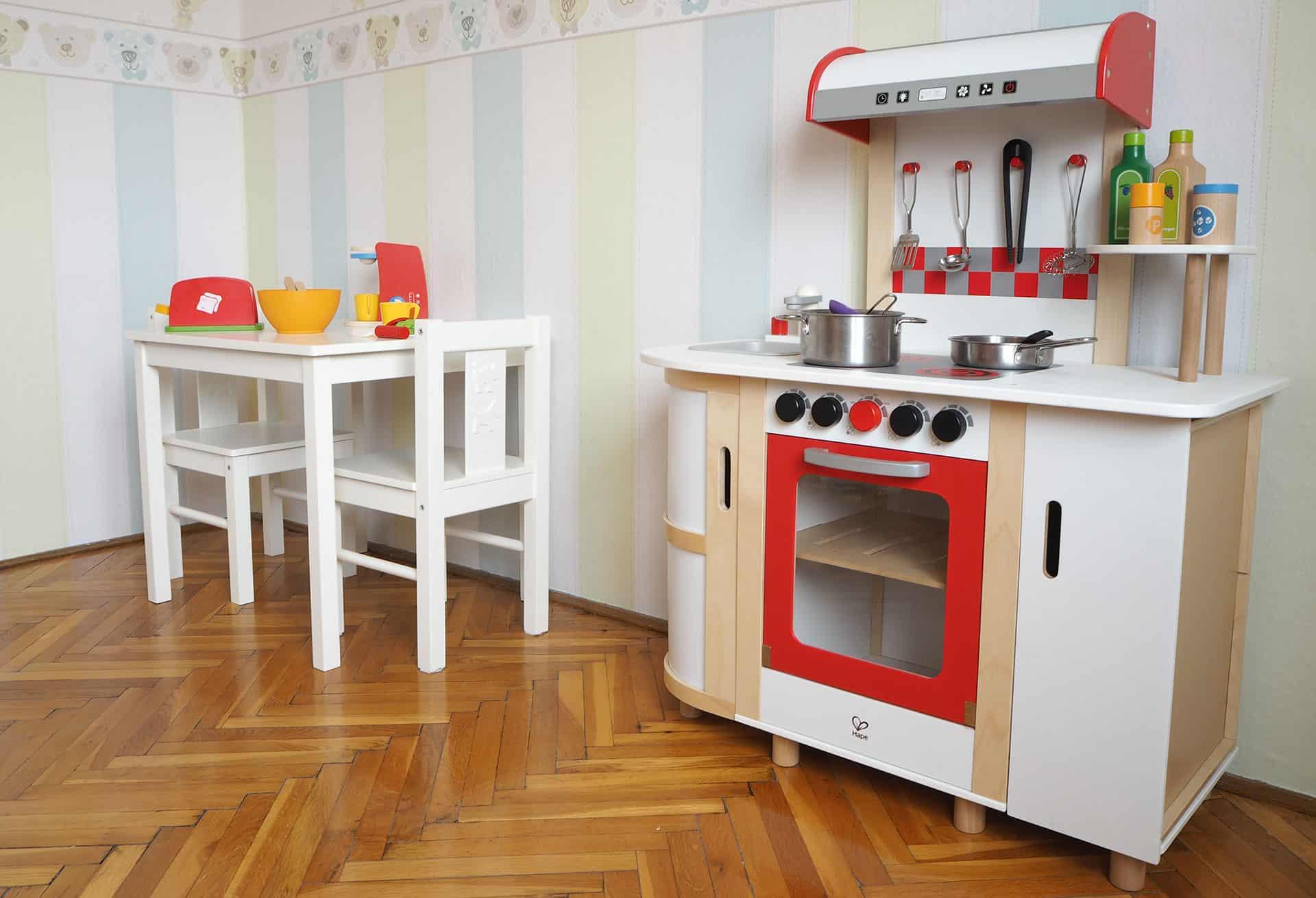 Die Hape Küchentraum Holzkinderküche neben einem Tisch mit Zubehör
