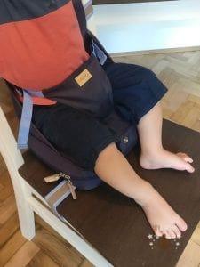 Kind sitzt im Roba Boostersitz auf einem Stuhl