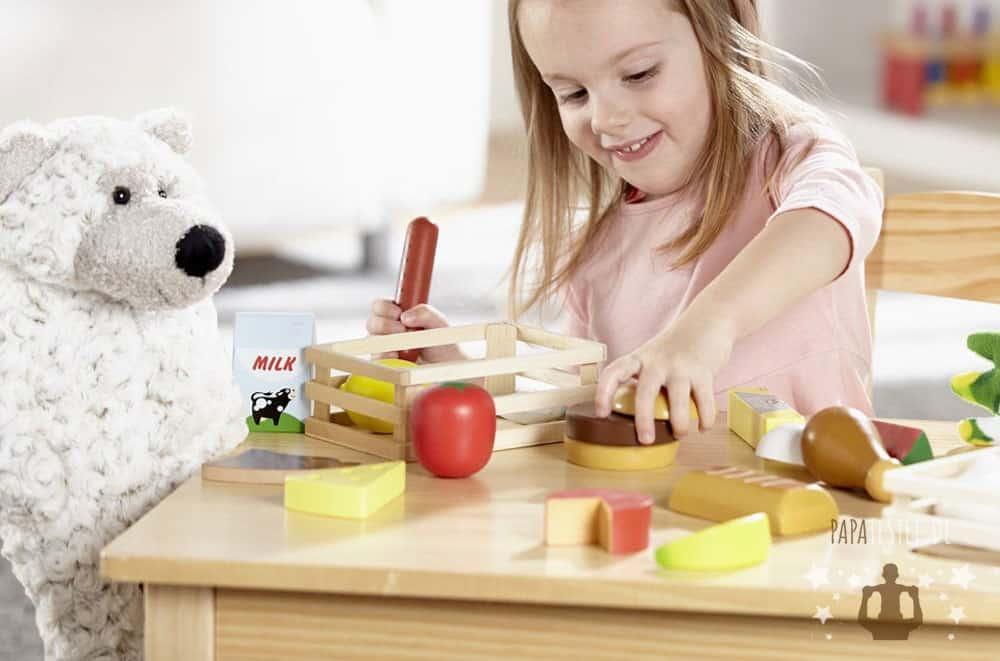 Ein Kind welches mit Spielküche Lebensmittel wie Obst, Gemüse, Pizza, Eier, Kuchen und Torten spielt